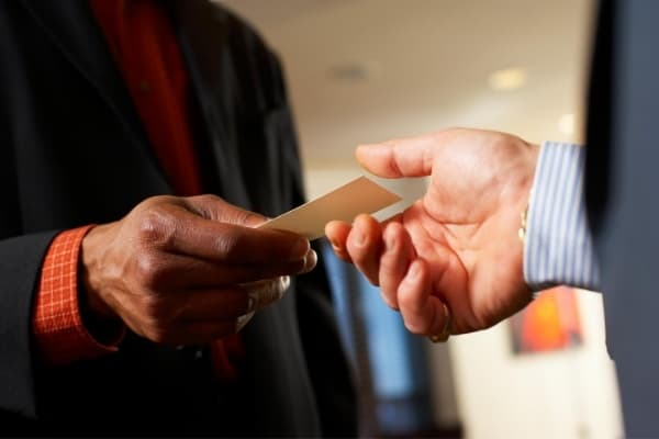 person handing a business card to another person